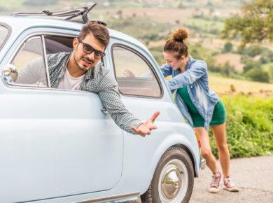 Ein Paar hat eine Autopanne und die Frau schiebt den Wagen an